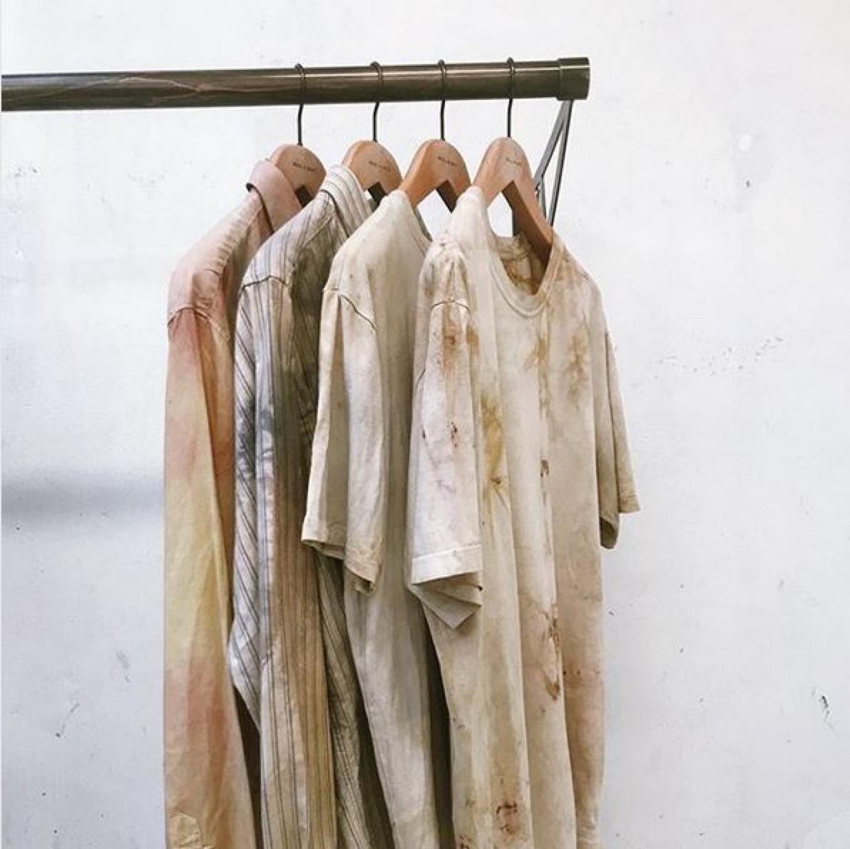 Impressie van de collectie: vier items op een rek, T-shirts en overhemden. Door het verfproves hebben ze verschillende pastelkleuren en zien ze er vlekkerig uit.