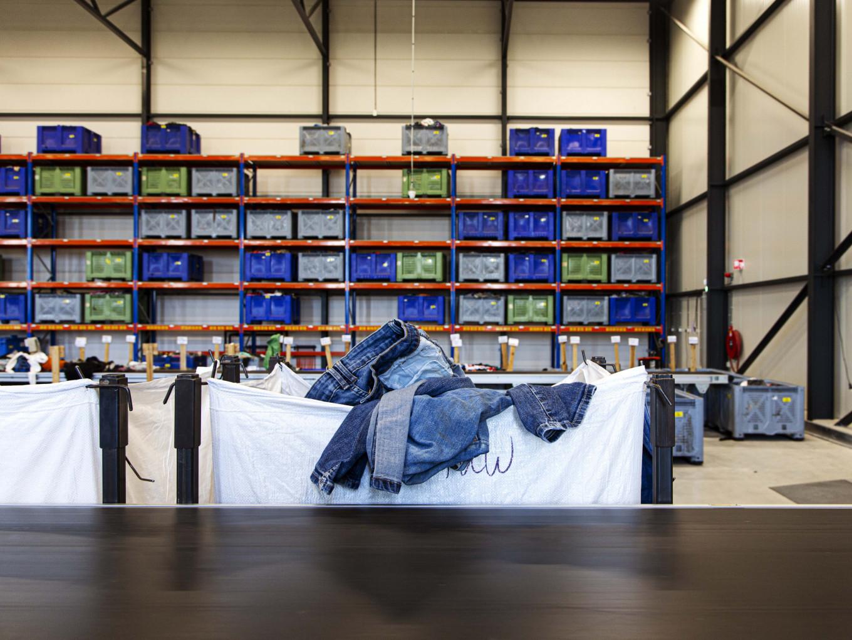 Textiel sorteercentrum waar grote bakken met kleding naast de lopende band staan