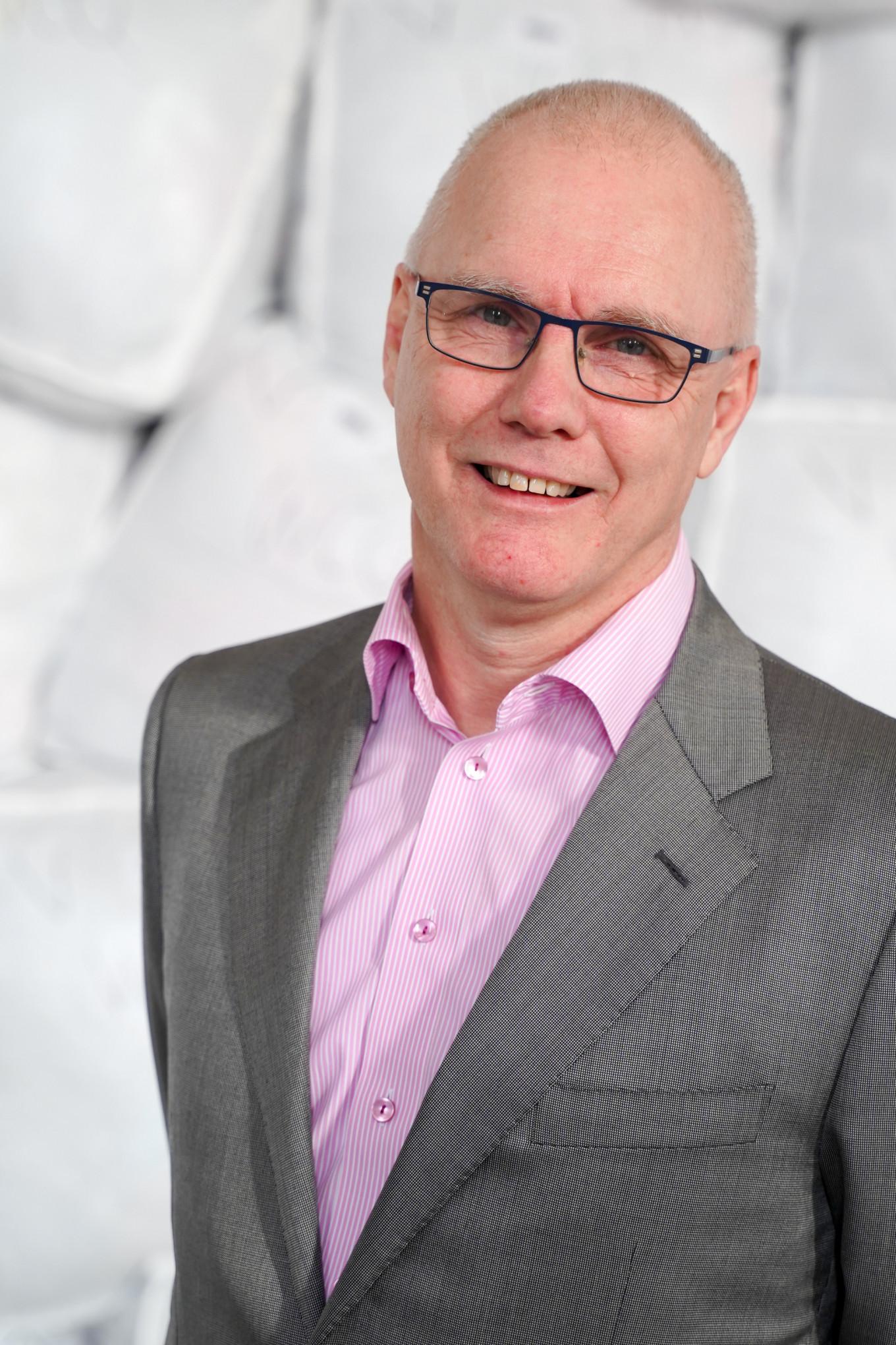 Een man met bril, haal hoofd, roze overhemd en grijs colbert glimlacht in de camera. Hij staat voor een berg met opgestapelde witte zakken die gevuld zijn met kleding en textiel.