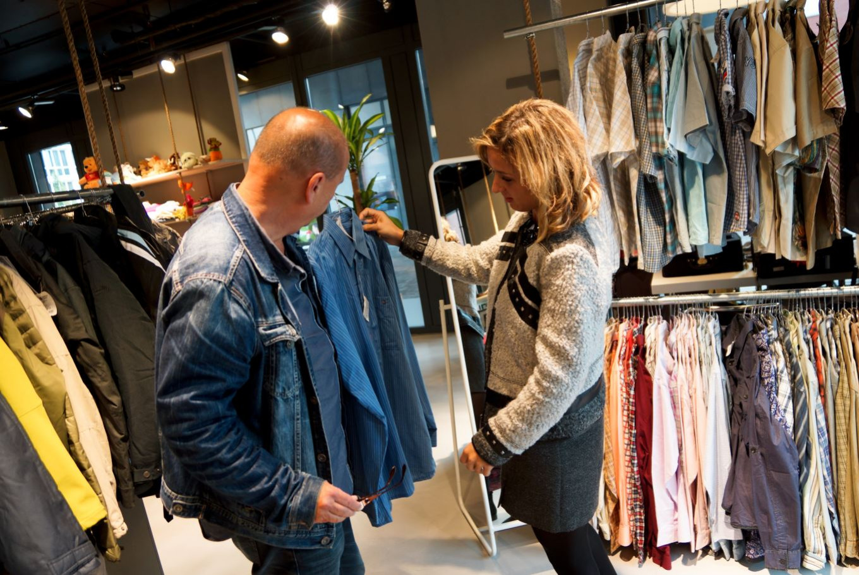Een man en een vrouw zoeken een jas uit in de ReShare Store
