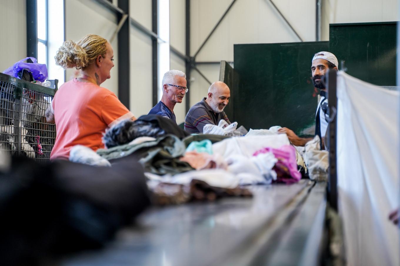 Aan de lopende band staan 3 mannen en een vrouw kleding te sorteren.