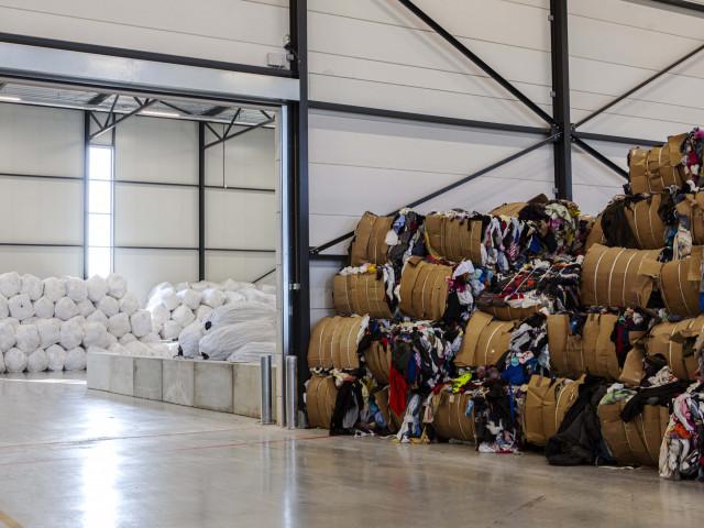 Een grote, licht loods met aan één zijde balen kleding en aan de andere kant grote gevulde witte bigbags