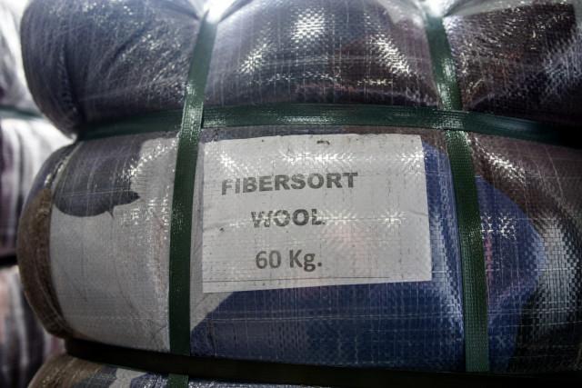 """Een grote plastic zak met stof waarop staat """"Fibersort Wool 60 kg"""""""