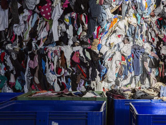 Een hele wand met opgestapeld afgedankt textiel, en gevulde textielcontainers ernaast.