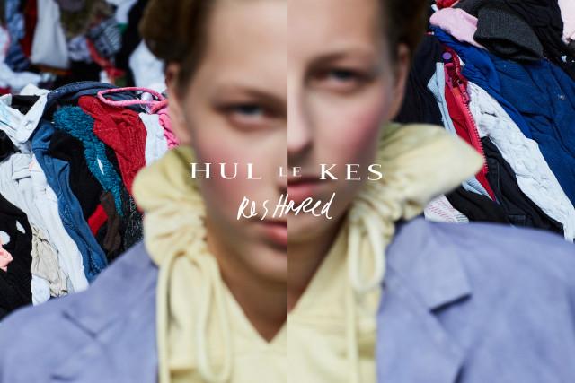 """Verstoorde portretfoto van een vrouw met op de achtergrond een hele berg kleding en de tekst """"Hullekes ReShared"""""""