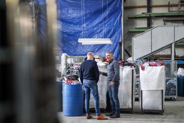 Twee mannen staan in een loods, naast een paar bakken kleding, met elkaar te praten.