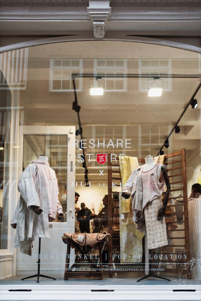 """Een foto van een etalageraam met daarop """"ReShare Store X Hul le Kes"""". Achter het glas is een kledingwinkel te zien."""