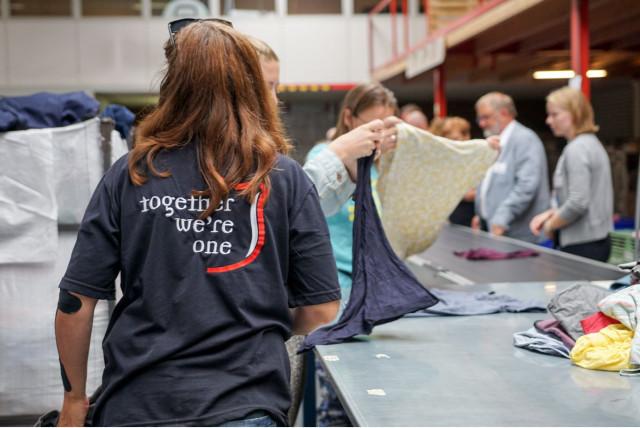 """Een sorteermedewerker van ReShare aan het werk met een vest waarop staat """"Together we are one"""""""