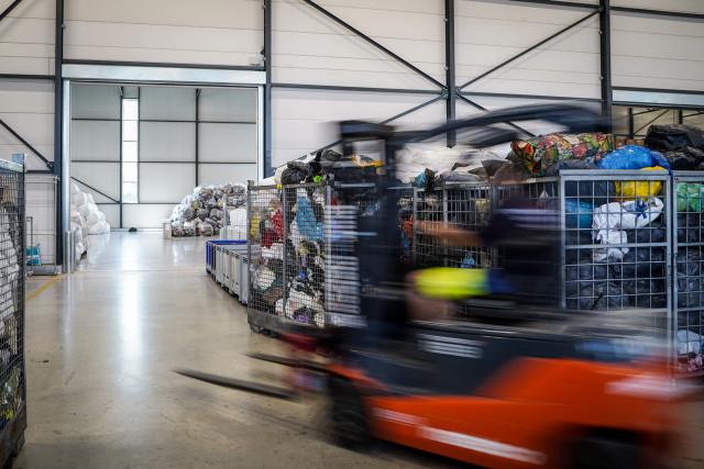 Vanuit een steekwagen wordt uitgekeken op een grote loods voor sortering en opslag van textiel
