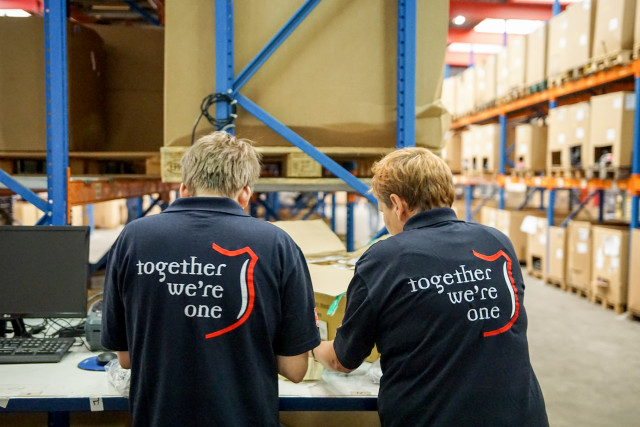 Twee mensen met Leger des Heils shirts zijn aan het werk in het sorteercentrum