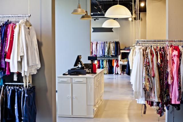 De ReShare Store van binnen: een ruime, lichte en overzichtelijke ruimte met kleding die op kleur en soort hangt.