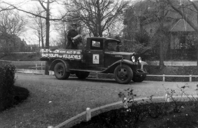 Een zwart-wit foto van een ouderweste pick-up die langs de huizen ging om gebruikte spullen en textiel op te halen voor het Leger des Heils